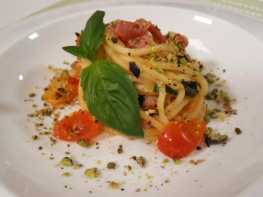 Spaghetti con pomodorini rossi e gialli, granella di pistacchi e pancetta croccante